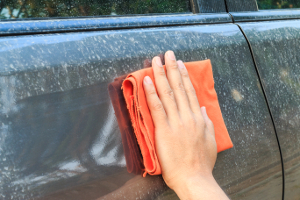 man wiping dirt off his car with a washcloth
