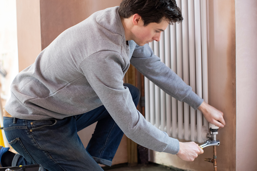 man fitting a vertical radiator
